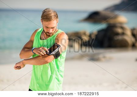 Young man using phone while listening to music at beach