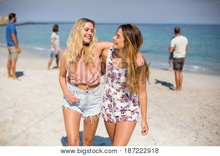 Happy female friends with arm around walking on shore at beach