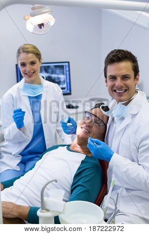 Portrait of dentists examining a male patient with tools in clinic