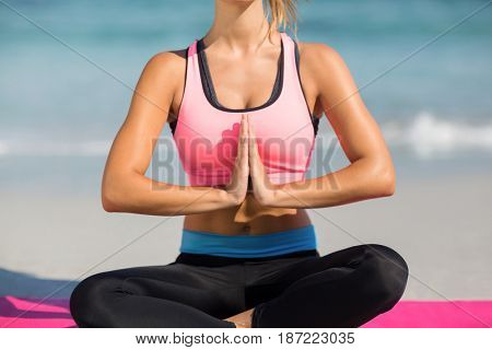 Midsection of young woman meditating while sitting at beach