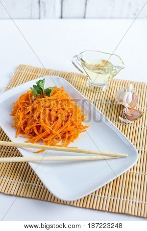 Korean carrots on white wooden table. The concept of healthy eating.