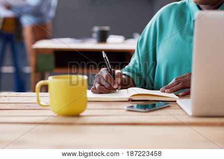 Closeup of an African businesswoman working on a laptop and writing down notes in a book while sitting at her desk in a modern office