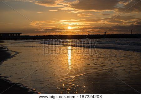 Sunset at the pier at the North Sea beach of Cadzand Holland