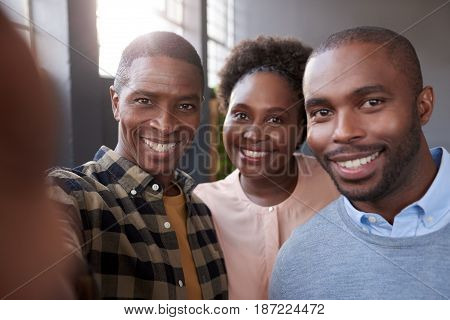 Three casually dressed young African businesspeople standing in a modern office smiling confidently while taking a selfie together in a large modern office