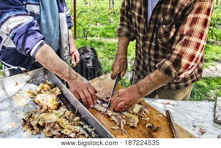 Dog calmly behind their backs watches to your boss while roasted meat cuts.