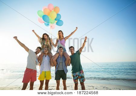 Portrait of happy friends with helium balloons at beach