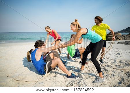 Friends helping man and woman while playing tug of war at beach