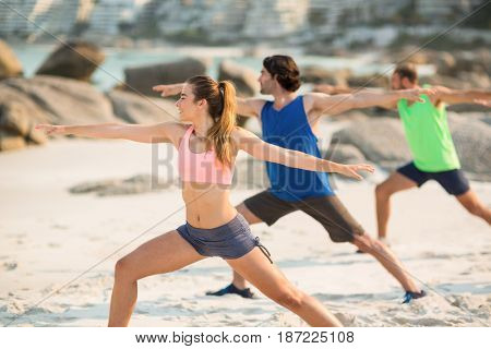 Friends practicing warrior pose on shore at beach