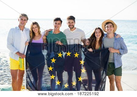 Portrait of happy friends holding European Union flag on shore at beach