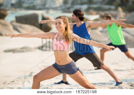 Friends practicing warrior 2 pose on shore at beach