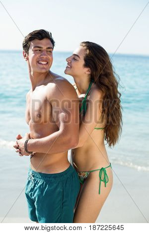 Side view of young woman embracing happy boyfriend at beach