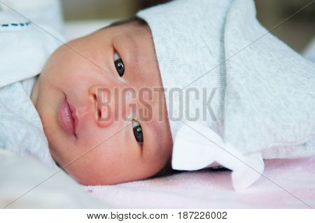 Focus at Asian baby girl with gray hat while sleeping and playing on the bed /  Close up at cute newborn is looking at camera