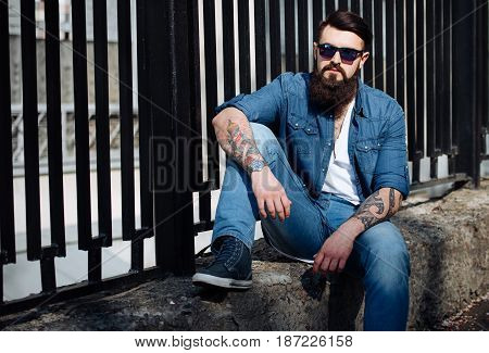 Brutal Bearded Man With Tattoo In Jeans Clothes Is Sitting Outdoors