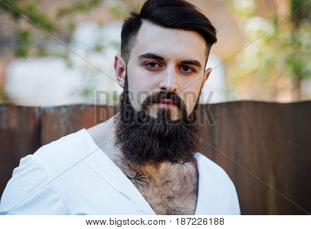 Portrait Of A Serious Brutal Stylish Bearded Man With Tattoo In White Tee-shirt Outdoors