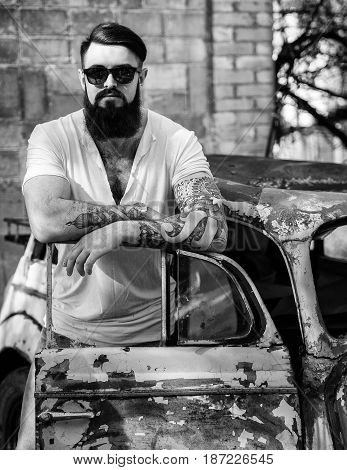Brutal Bearded Man With Tattoo In Jeans And White Tee-shirt Standing Near The Old Car