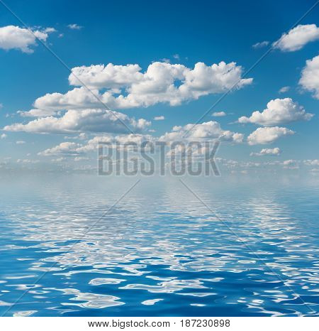 Vast blue summer sky with fluffy white cumulus clouds reflected in a water surface with small waves