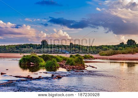 Flowing river and smoke on the far shore in the evening at dusk
