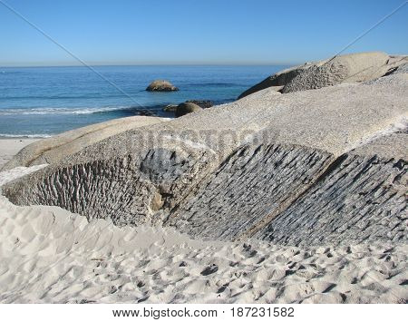 CAMPS BAY, CAPE TOWN, SOUTH AFRICA, UNUSUALLY SHAPED BOULDERS IN FORE GROUND
