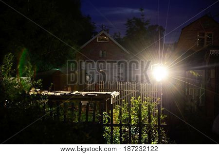 Lights from spotlight at night in backyard of rural house.