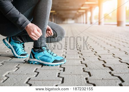 Female Runner Tying Shoe Lace In A Urban Area.