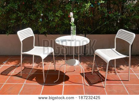Empty table and chairs in outdoor. Table and chairs made of white painted steel. white rose in vase on the table.