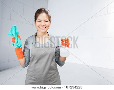 Asian Housewife Holding Spray Bottle And Rag