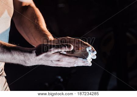 Male Powerlifter Hand In Talc And Sports Wristbands Preparing To Bench Press