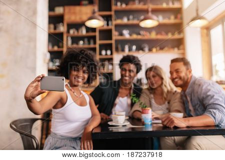 Multiracial Friends Taking Selfie On Smart Phone At Cafe