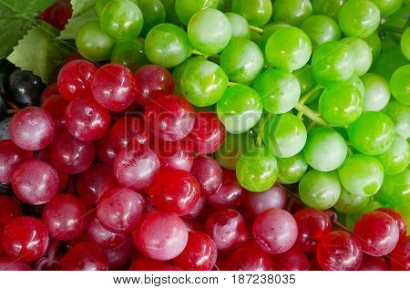 Fake plastic bunch red and green of grapes fruit. Can be use for background.