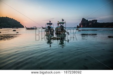 KO PHI PHI, THAILAND, January 31, 2014: Traditional long tail boats on the beach at sunset, Ko Phi Phi, Andaman Sea, famous tourist destination in Thailand