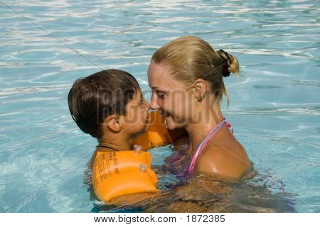 Son And Mom Swim And Play In The Pool