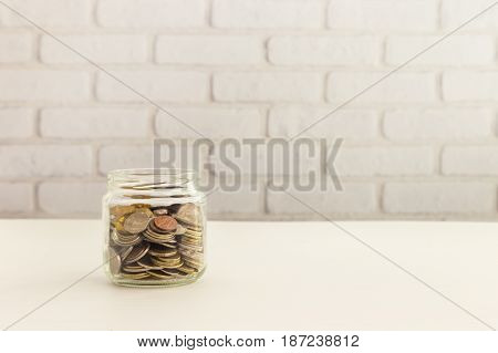 Saving money jar world coins in glass container with white bricks wall background.