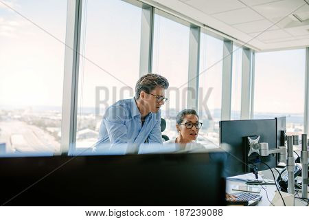 Mature asian businesswoman working on desktop computer with male colleague. Two office worker working together on computer.