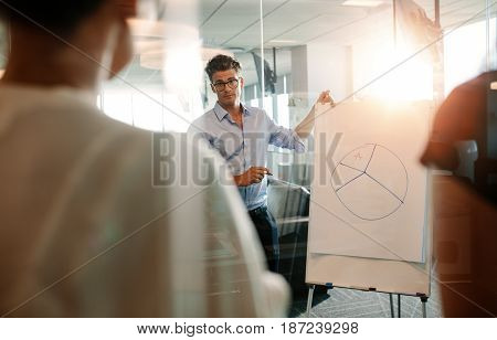 Manager explaining pie chart to coworker in modern office. Mature executive giving presentation to colleagues over flip chart.