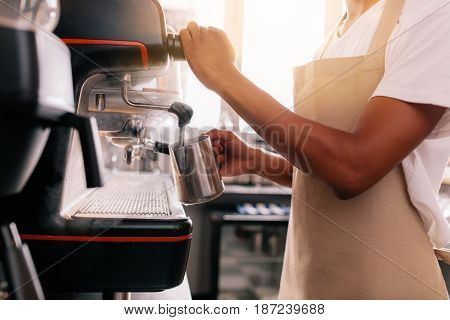 Close up of young man preparing coffee on machine. Barista holding metal jug warming milk using the coffee machine.