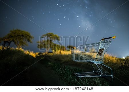 shopping wagon cart under stars of Milky Way  galaxy