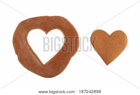 Heart shaped cookie next to a rolled up layer of dough with a cut out, composition isolated over the white background