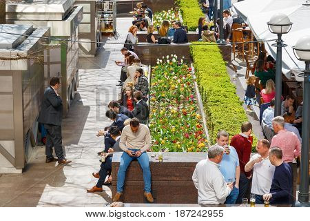 An Outdoor Space In Canary Wharf Packed With People Drinking And Chatting