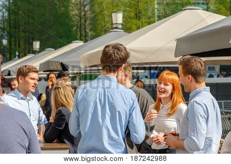 London UK - May 10 2017 - A young businesswoman drinking with her colleagues at a packed outdoor bar in Canary Wharf on a sunny day