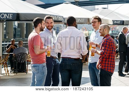 Group Of Young Men Drinking At A Dockside Bar