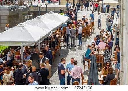 An Outdoor Bar In Canary Wharf Packed With People Drinking And Chatting