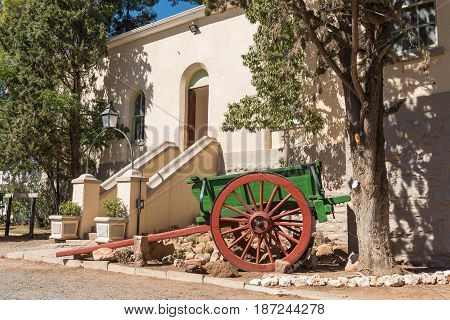 An historic horse or ox drawn cart in front of the historic station building in Matjiesfontein now a museum