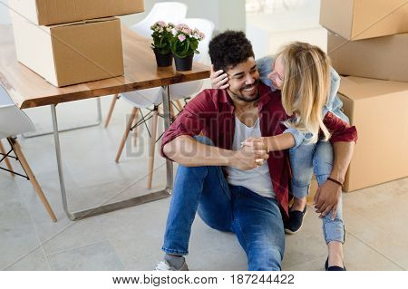 home, people, moving and real estate concept - happy couple having fun while moving in new apartment