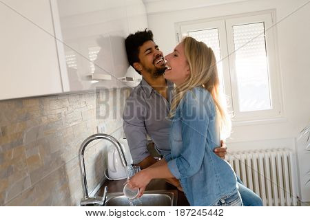 Young couple in love doing dishes in the kitchen and smiling