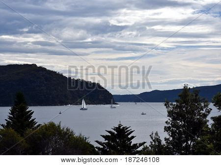 West Head lookout on the other side of the bay. Yach sailing on the water. View from Palm beach.