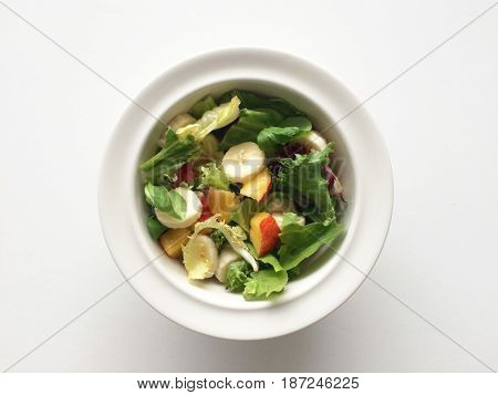 A bowl of fresh healthy fruit and vegetable salad with mixed leaves nectarine and banana on a white table.