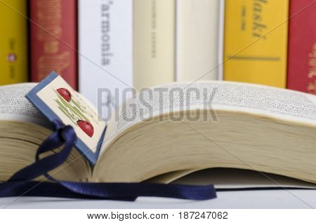 close up of an open book with bookmark and books in the background lining in a row