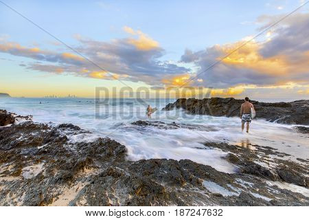Surfers going into the ocean as the ocean tide washes over the rocks at Currumbin Rock, Gold Coast