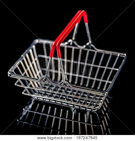 concept of black friday advert sale empty metal shopping basket isolated on black background close up