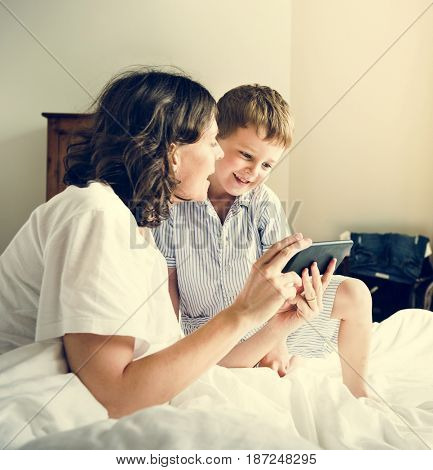 Son and Mom Using Smart Phone in Pyjamas